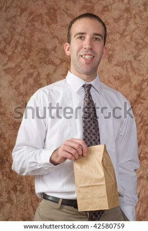 A young employee wearing a white shirt and tie, holding his paper bagged lunch - stock photo