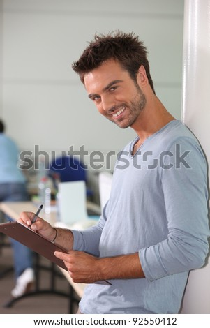 A young employee writing on a notepad and looking at us. - stock photo
