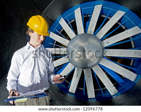A young engineer, reporting in after completing his inspection of a huge industrial wind tunnel - stock photo