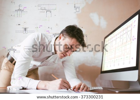a young engineer working on a draft, drawings come from a drawing, Construction drawings - stock photo