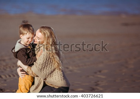 A young fair-haired woman is sitting on her haunces on the sand, embracing her small son and trying to kiss him. Clothes: casual. - stock photo