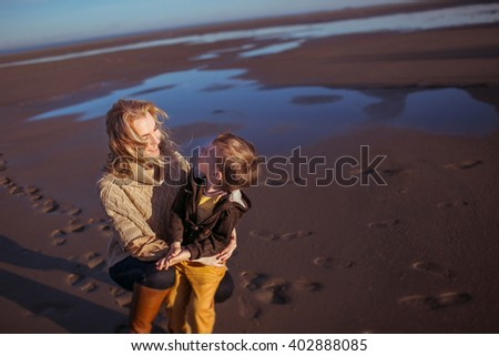 A young fair-haired woman is sitting on her haunches on the wet sand in a sunny day, embracing her small son and smiling. Clothes: casual. - stock photo