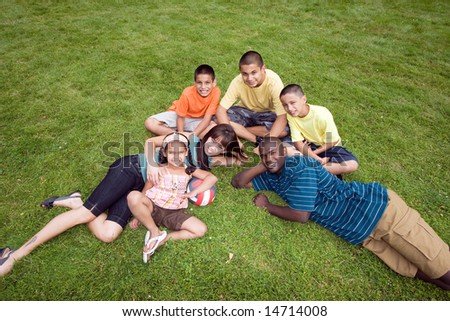 A young family, all sit and lie in the grass together, smiling. - horizontally framed - stock photo