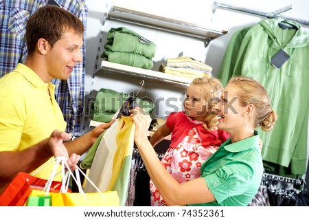 A young family choosing clothing in the shop - stock photo