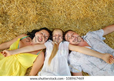 A young family, father, mother and daughter. Lie on hay - stock photo