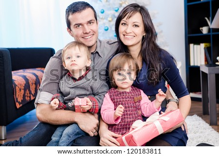 a young family getting Christmas gifts - stock photo