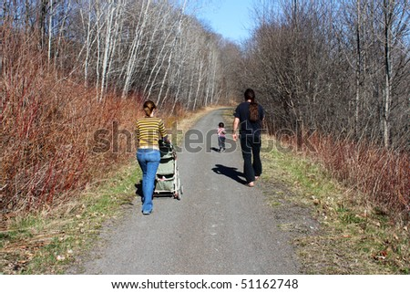 A young family going for a walk on a rural path - stock photo