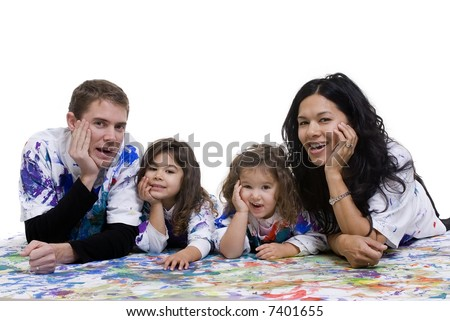 A young family having fun painting on the floor - stock photo