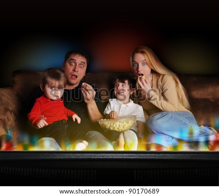A young family is watching television and having movie night on the couch at home. The background is black and there are 2 children