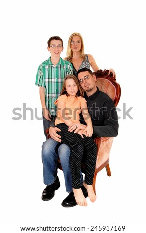 A young family, mom, dad, daughter and son, isolated for white background sitting in a pink armchair.
