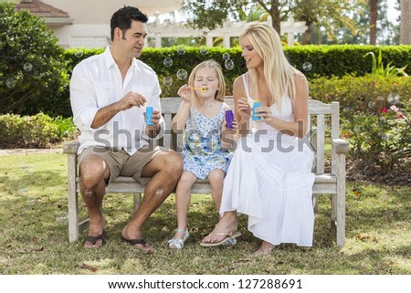 A young family mother & father parents with girl child blowing bubbles having fun together sitting on a bench in a sunny park or garden. - stock photo