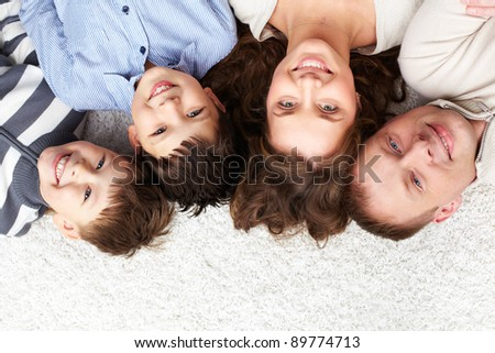 A young family of father, mother and two kids looking at camera - stock photo