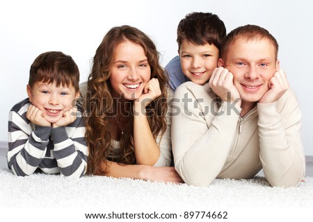 A young family of father, mother and two kids posing in front of camera
