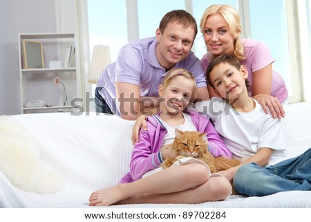 A young family of four with a cat sitting on sofa, looking at camera and smiling - stock photo