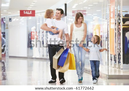 A young family of four with children in the store - stock photo