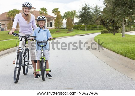A young family of woman and boy child, mother and son, cycling together. - stock photo