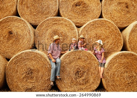 a young family on haystacks in cowboy hats - stock photo