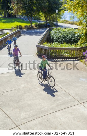 A young family seen from above ride single file along a bike path with a river in the background. - stock photo