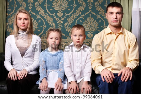 A young family sitting in row and looking at camera