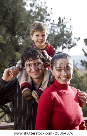 A young family together outside enjoying the outdoors - stock photo