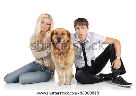 A young family with a dog breed golden retriever sitting on floor, looking at camera