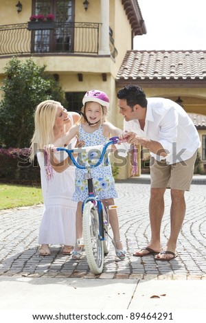 A young family with girl child riding a bicycle and her happy excited parents giving encouragement alongside her - stock photo