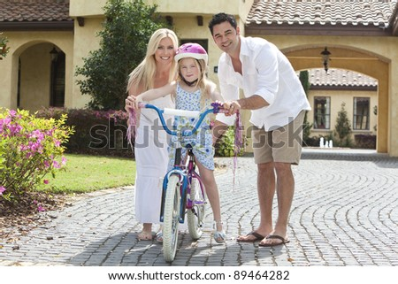 A young family with girl child riding a bicycle and her happy parents giving encouragement - stock photo
