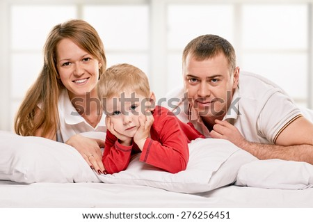 A young family with little daughter to bed in the bedroom on window background - stock photo