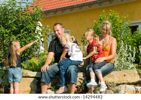 A young family with three children in front of their new home sitting in the sun - stock photo