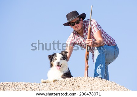 A young farmer with his rifle and sheep dog on the lookout for coyotes that kill his livestock - stock photo