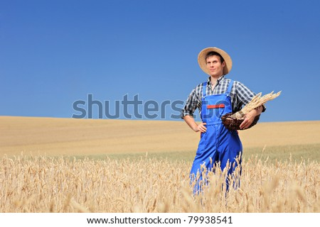 A young farmer with panama hat holding a basket in a wheat field - stock photo