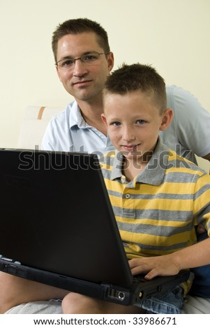 A young father and his son working together on a laptop. - stock photo