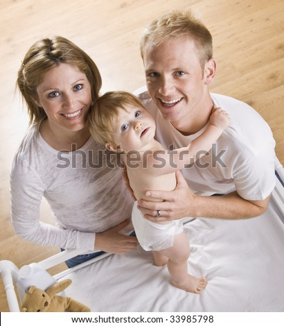 A young father and mother are holding their baby daughter on her changing table. They are looking up and smiling at the camera.  Square framed shot. - stock photo