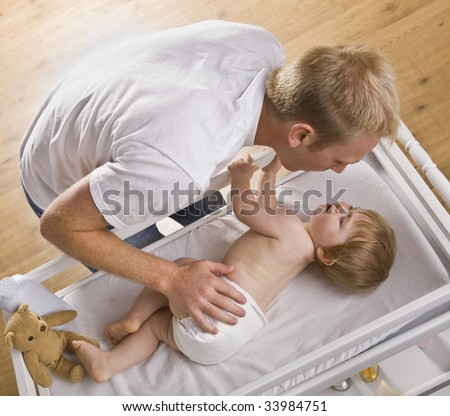 A young father is changing his baby daughter's diaper.  They are looking at each other.  Square framed shot. - stock photo