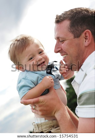 A young father is holding and playing with his son.  He is looking at the child and his son is looking away from the camera.  Vertically framed shot. - stock photo