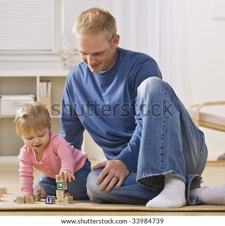 A young father is on the floor playing with his daughter.  He is smiling and looking at her.  Square framed shot. - stock photo