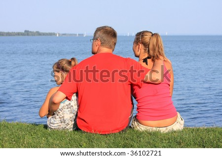 A young father looks at the sailboats with his girls - stock photo