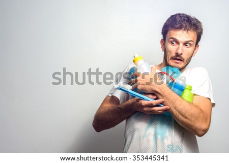 A young father scared holding several baby stuff - stock photo
