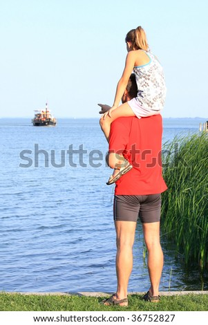A young father shows his little girl the boat - stock photo