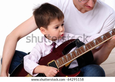 A young father teaches his young son to play guitar - stock photo