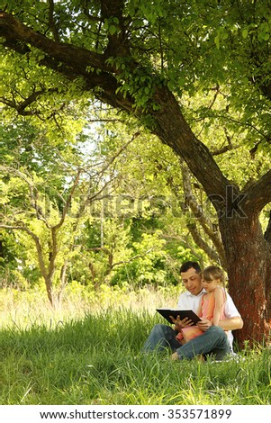 a young father with a small daughter reading the Bible