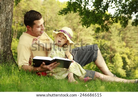 a young father with his little daughter reads the Bible - stock photo