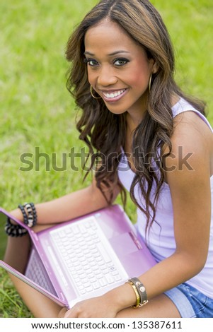 A young female african-american woman working on her laptop computer, enjoying a day at the park - stock photo