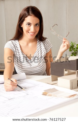 A young female architect at a desk with blueprints and model house - stock photo