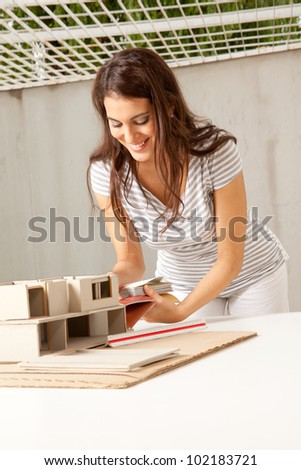 A young female architect choosing color swatches for a building - stock photo