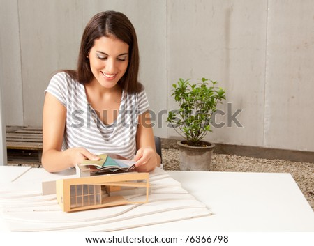 A young female architect looking at color swatches with a model house - stock photo