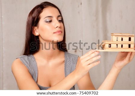 A young female architect or designer looking at a rough house model - stock photo