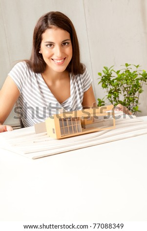 A young female architect smiling at the camera with a house model - stock photo