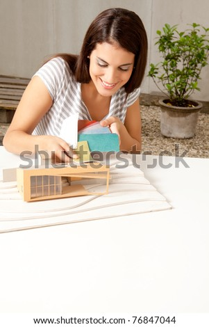A young female architect testing a color swatch on a model house - stock photo