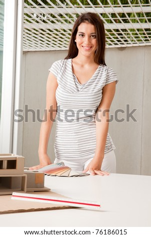 A young female architect with color swatches and a rough model - stock photo